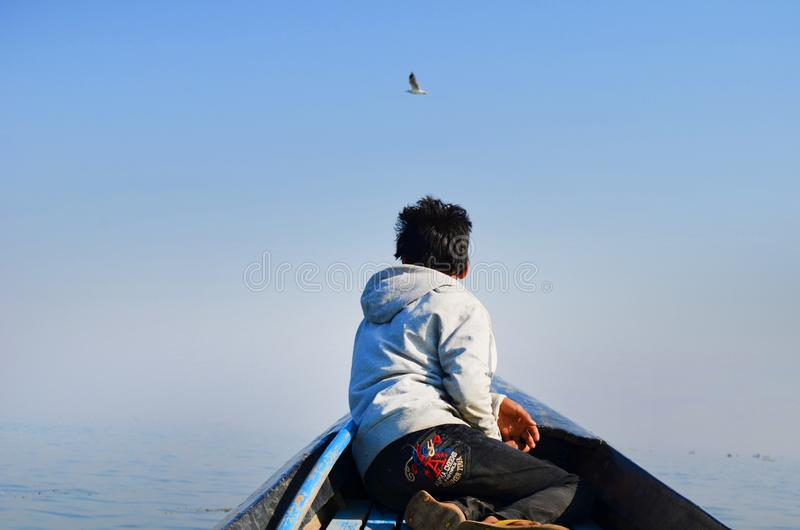Man in Grey Hoodie and Black Pants Sitting in the Middle of Boat Looking at Bird in the Sky stock images