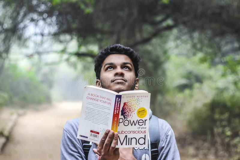 Man in Grey Shirt Holding Opened Book Looking Upward royalty free stock photos