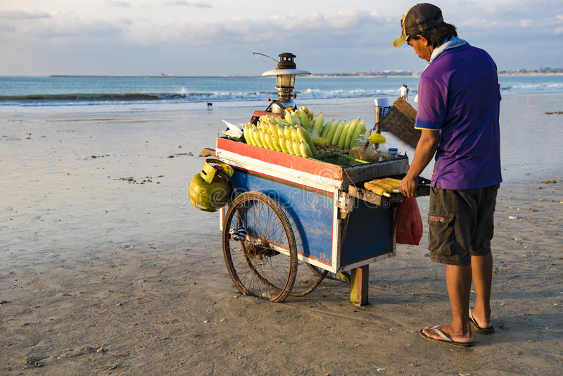 Man grilling corn at beach in Bali. Balinese man selling grilled corn at beach in Bali stock images