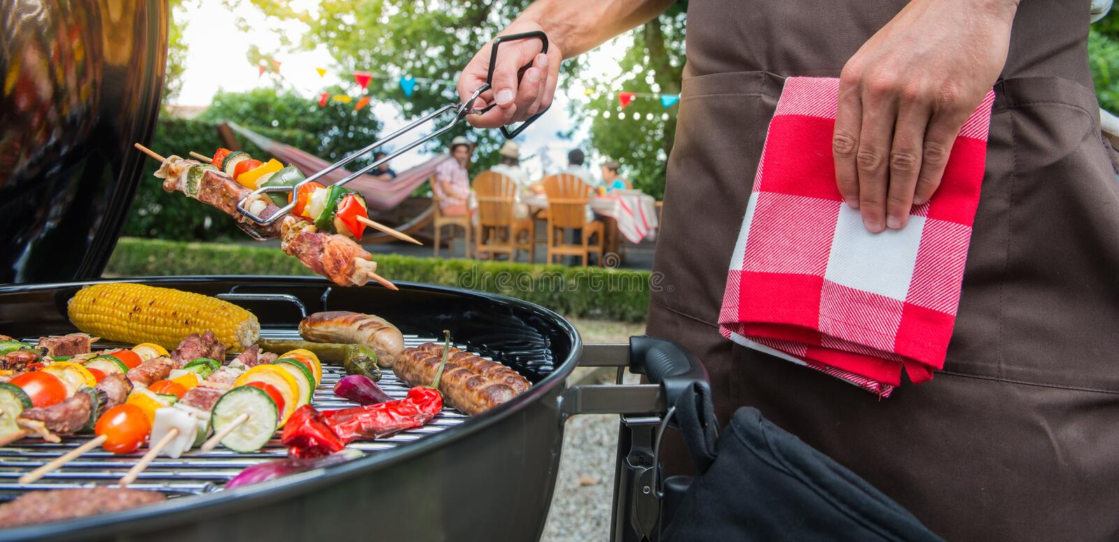 Man grilling meat on garden barbecue party. In the background friends eating and drinking royalty free stock photos