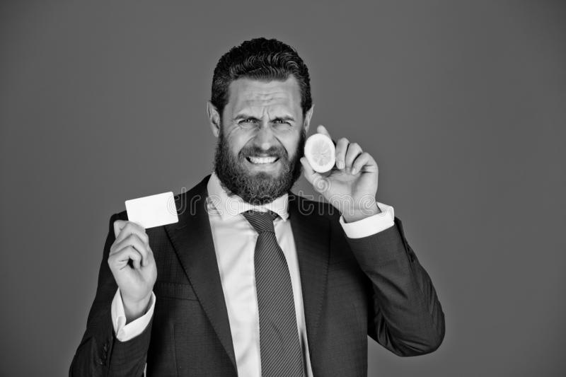 Man with sour lemon fruit, holding business or credit card. Man with grimace bearded face from sour lemon fruit, holding business or credit card in hand royalty free stock photo