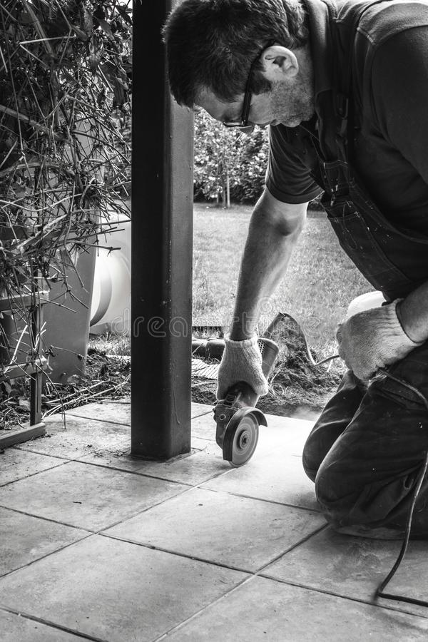 Man worker grinder cutting a tile on veranda stock images