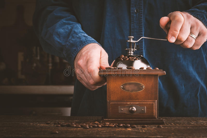 Man grinding coffee in coffee mill horizontal stock photography
