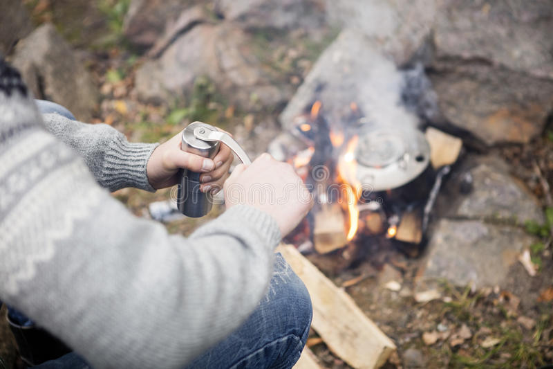 Man Grinding Coffee Near Bonfire At Campsite. High angle midsection of man grinding coffee near bonfire at campsite stock image