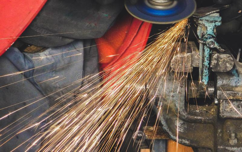 Man Grinding metal part with electric grinder making a lot of sparks stock photos