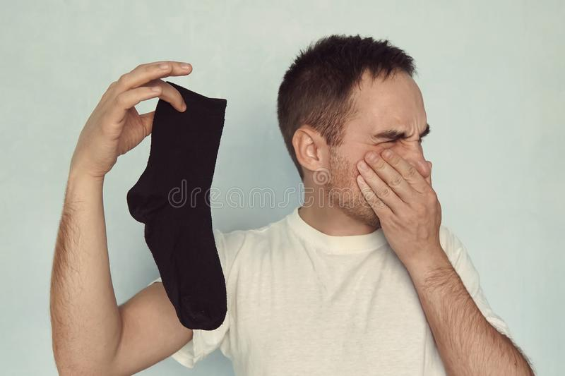 Man grips nose with fingers holding a smelly sock in hand royalty free stock image
