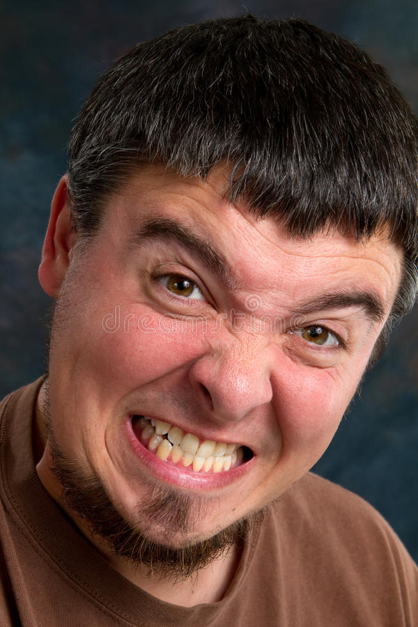 Man Gritting Teeth. Man grits his teeth with a painful expression stock photo