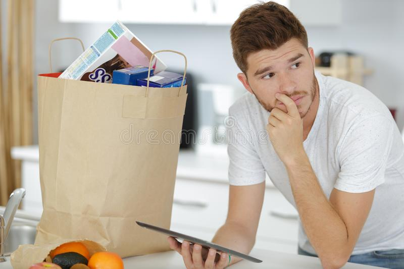 Man after grocery shopping using digital touch screen tablet stock images