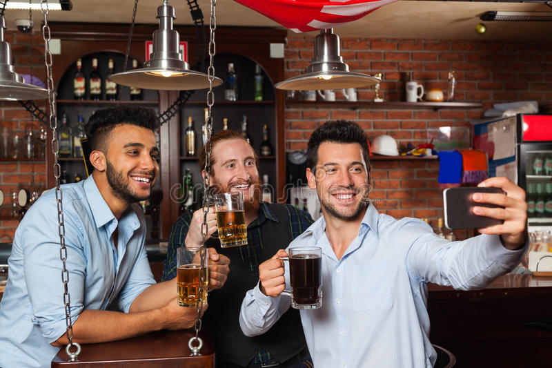 Man Group In Bar Taking Selfie Photo, Drinking Beer, Mix Race Cheerful Friends Meeting Communication. Guy Hold Smart Phone royalty free stock photos