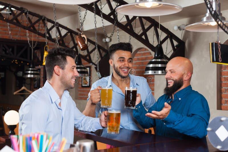 Man Group i stång rymmer exponeringsglas som talar och att dricka öl, rånar, skjortor för kläder för vänner för blandningloppet g royaltyfri bild