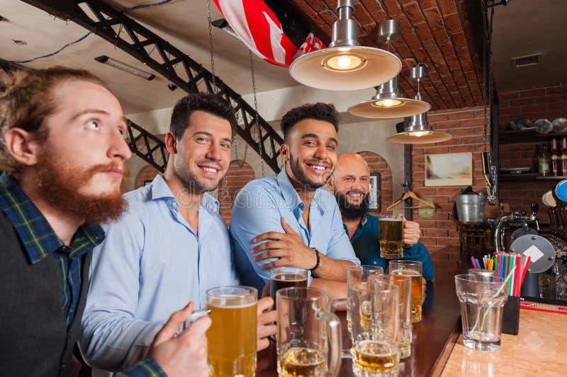 Man Group i stång rymmer lyckligt le för exponeringsglas och att dricka öl, möte för vänner för blandninglopp gladlynt royaltyfria bilder