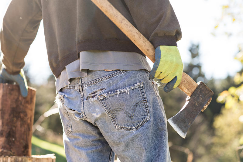 Man in grunge blue jeans chopping wood stock photos