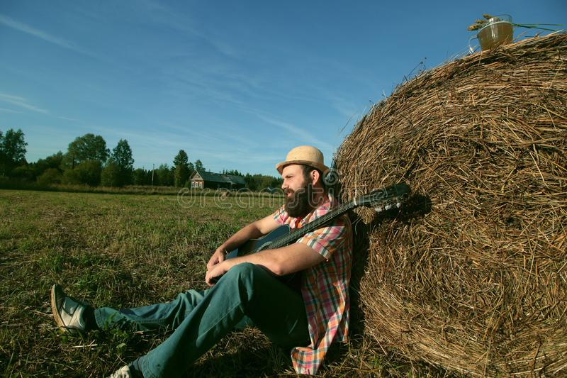 Man with guitar and beer on nature. Man with guitar and beer on the nature stock photography