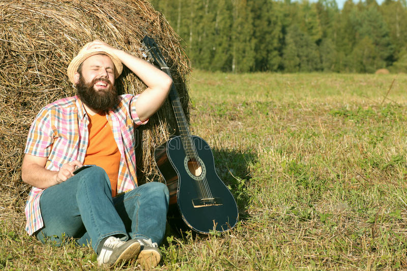 Man with guitar and beer on nature. Man with guitar and beer on the nature royalty free stock image