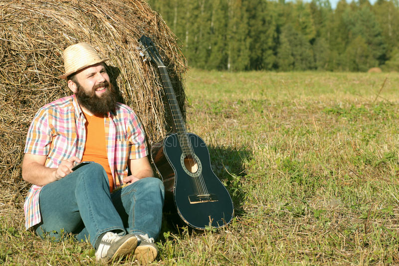 Man with guitar and beer on nature. Man with guitar and beer on the nature royalty free stock photos