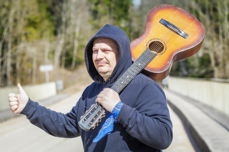 Man with guitar on shoulder try to stop car. In summer day royalty free stock photo