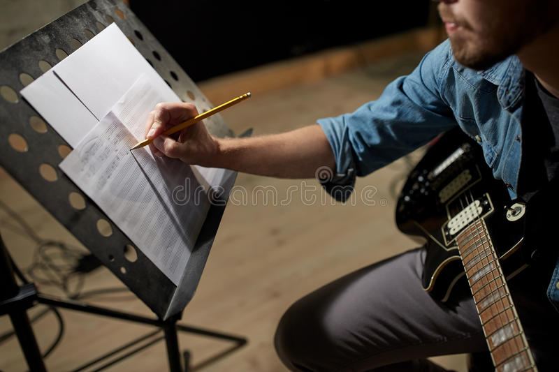 Man with guitar writing to music book at studio stock photo