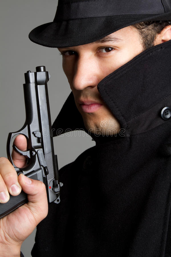 Man With Gun. Suspicious sneaky man with gun royalty free stock photography