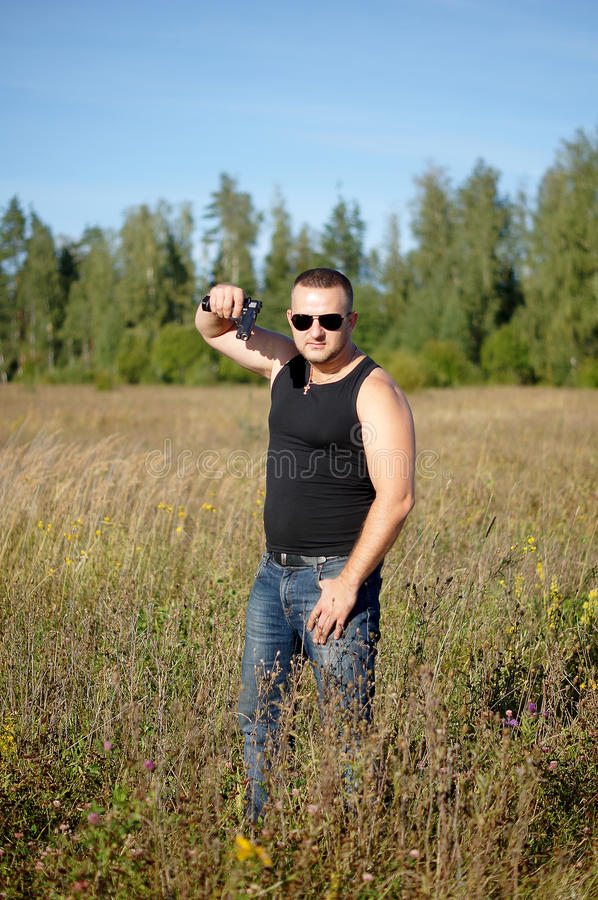A man with a gun in his hands. Outdoor portrait stock photo