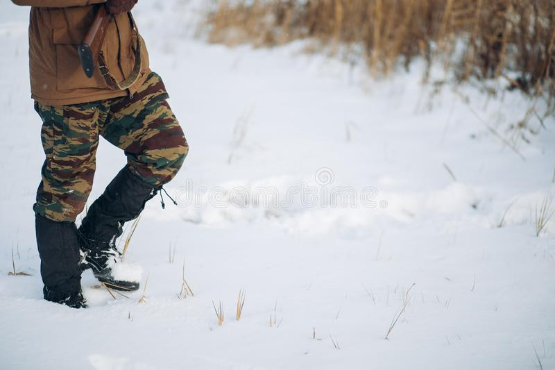 Man with a gun is walking on a snowy field. Close up cropped sside view photo. man with a gun is walking on a snowy field. copy space. guy is spending time in royalty free stock photo