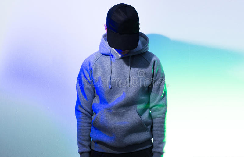 The man, guy in the blank black , baseball cap, grey hoody, on royalty free stock photography