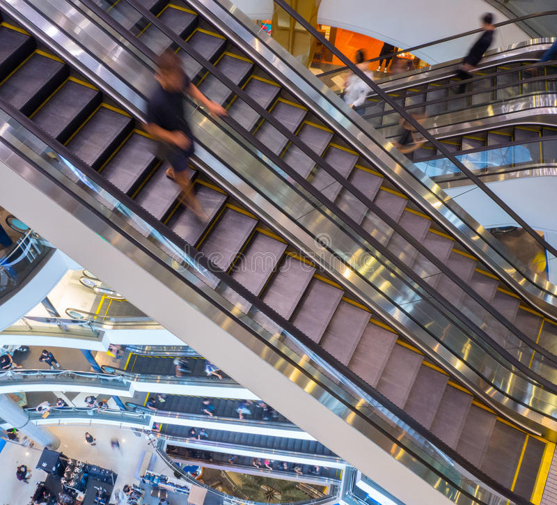 Man guy people rushing step in motion on escalator in the mall building stock image