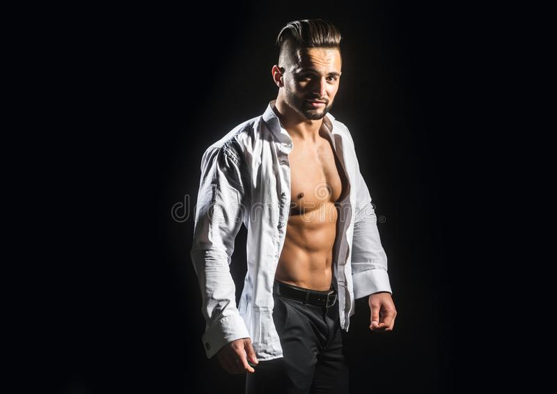 Man. Guy in a white shirt on a black background. Young businessman with a stylish hairstyle. Male model. Athlete from a. Beautiful strong body in an informal royalty free stock images