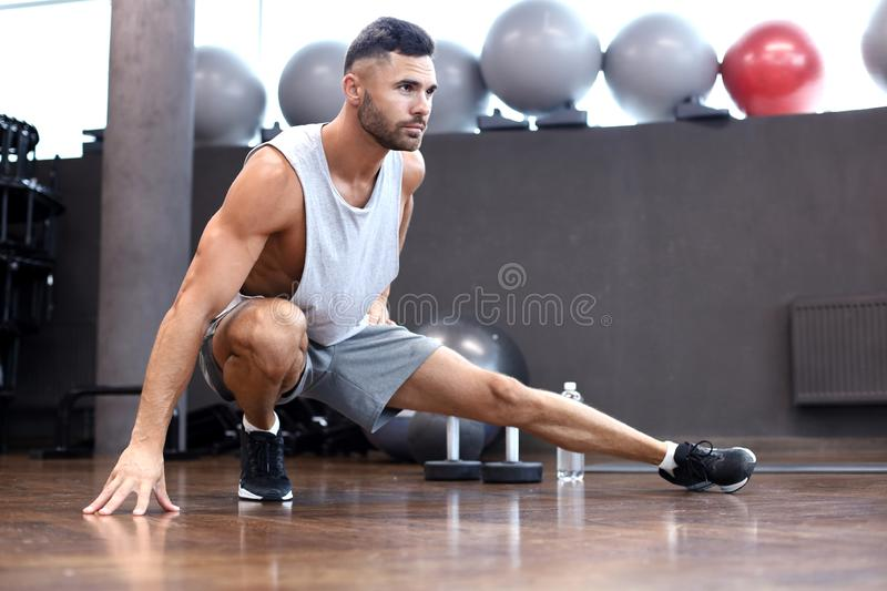 Man at the gym doing stretching exercises on the floor. Man at the gym doing stretching exercises on the floor royalty free stock photos