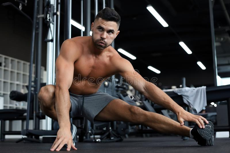 Man at the gym doing stretching exercises on the floor. Man at the gym doing stretching exercises on the floor stock photos