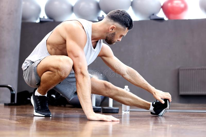 Man at the gym doing stretching exercises on the floor.  royalty free stock photo