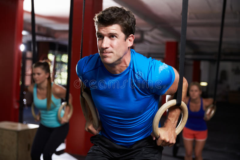 Man In Gym Exercising With Gymnastic Rings stock photos