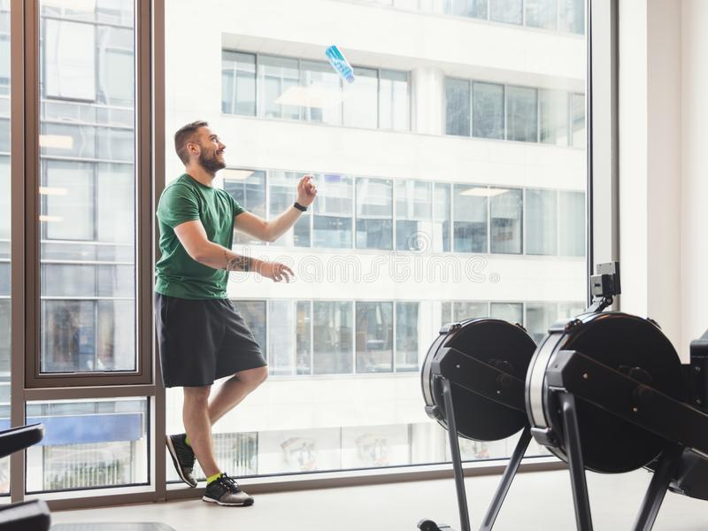 Man in a gym throwing a bottle up in the air. royalty free stock image