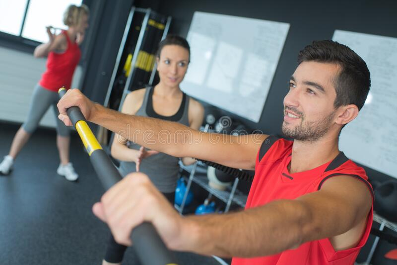 Man in gym training with stick royalty free stock photo
