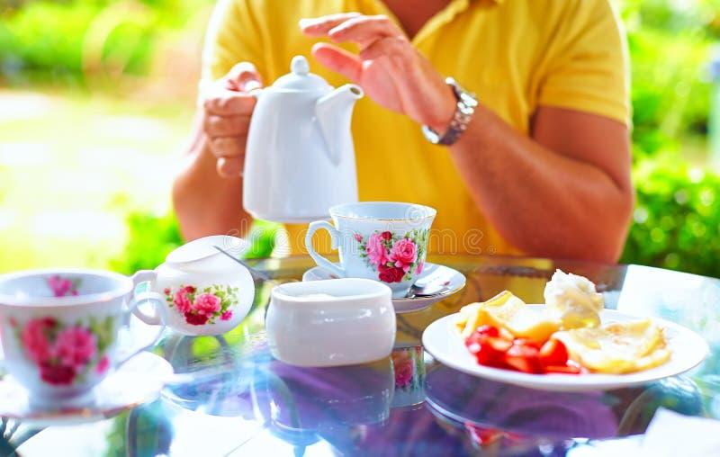 Man hällande engelskt te i kopp, på sommarträdgården arkivbild