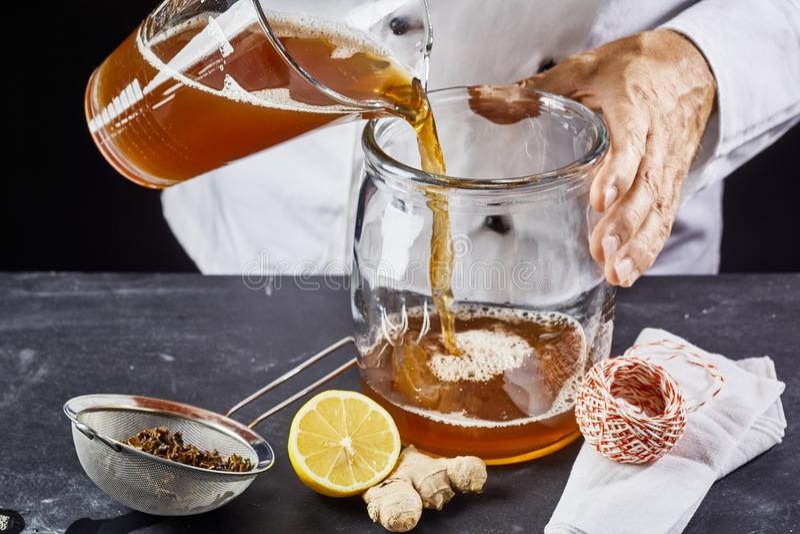Man hällande te för kombuchaen SCOBY in i kruset arkivfoton