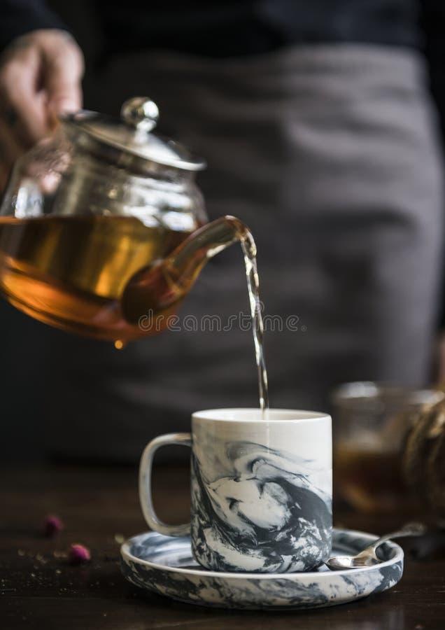 Man hällande te in i en kopp arkivbilder