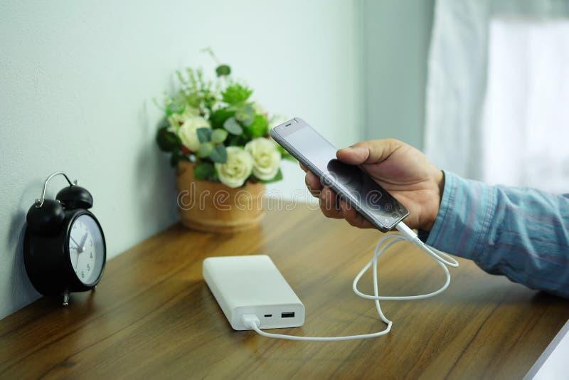 Man hält Smartphone und Backup-Power-Bank auf dem Schreibtisch Holztisch bereit stockbilder