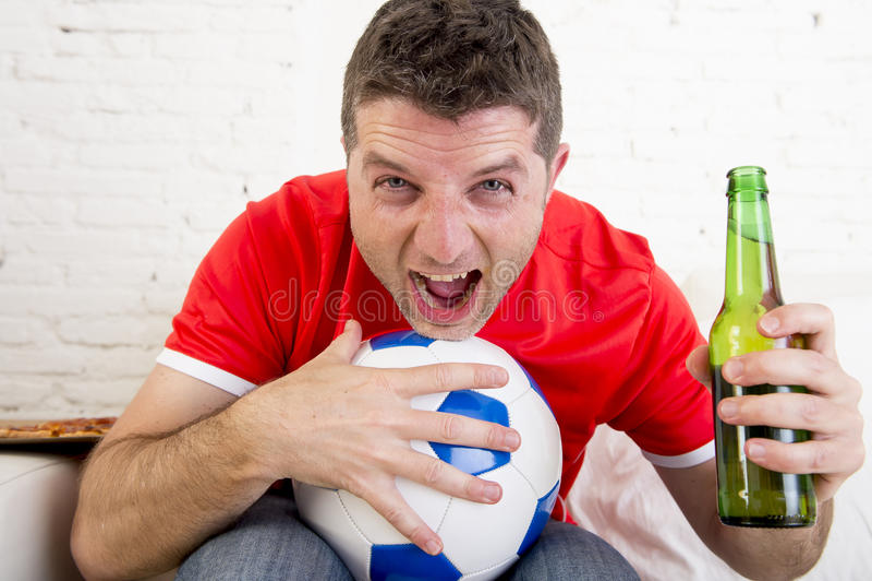 Man hållande ögonen på fotboll på den bärande lagärmlös tröja för tv som firar målet som är lyckligt på soffan royaltyfria bilder