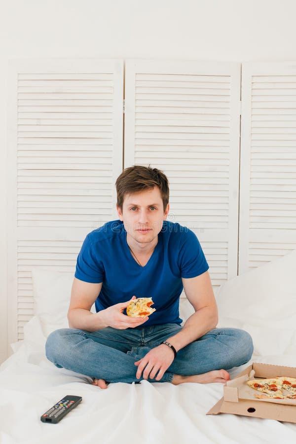 Man hållande ögonen på TVsammanträde på sängen och ätapizza royaltyfria bilder
