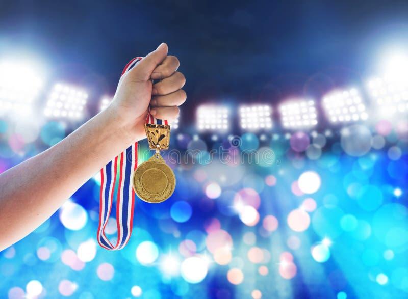 Man hållande övre en guldmedalj mot, segerbegreppet royaltyfri foto