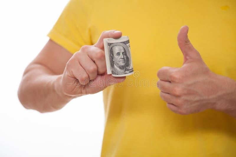 Man hållande dollar och visningen en tumme upp tecken royaltyfri foto