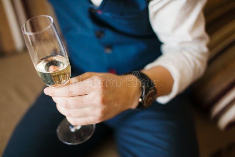 Man hållande exponeringsglas av champagne i hand på soffan arkivbild