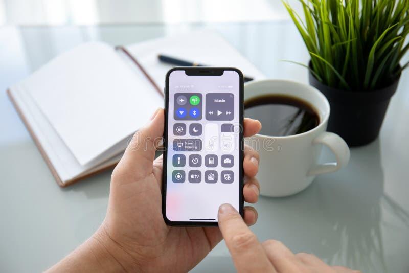 Man hållande iPhone X för handen med startskärmen Control Center royaltyfri bild