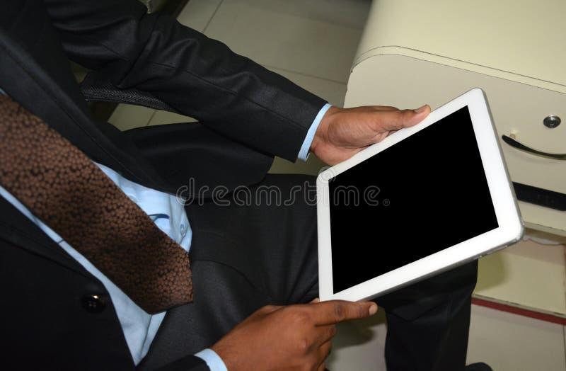 Man hållande och att bläddra den tomma skärmen för minnestavlaPC:n royaltyfri foto