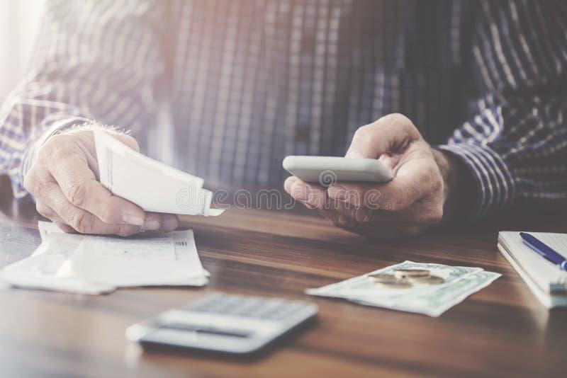 Man hållande pengar och att använda mobiltelefonkassapapper och mynta pengar royaltyfria foton