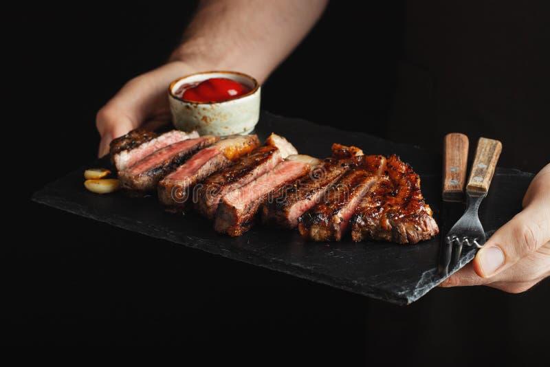 Man hållande saftig grillad nötköttbiff med kryddor och röd sås på en stenskärbräda på en svart bakgrund arkivfoto
