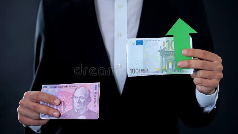 Man hållande sedlar, euroet som växer relativt till schweizisk franc, finansiell prognos arkivbild