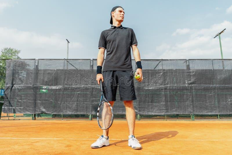 Man hållande tennisbollar och racket, medan koppla av efter turnering royaltyfri foto