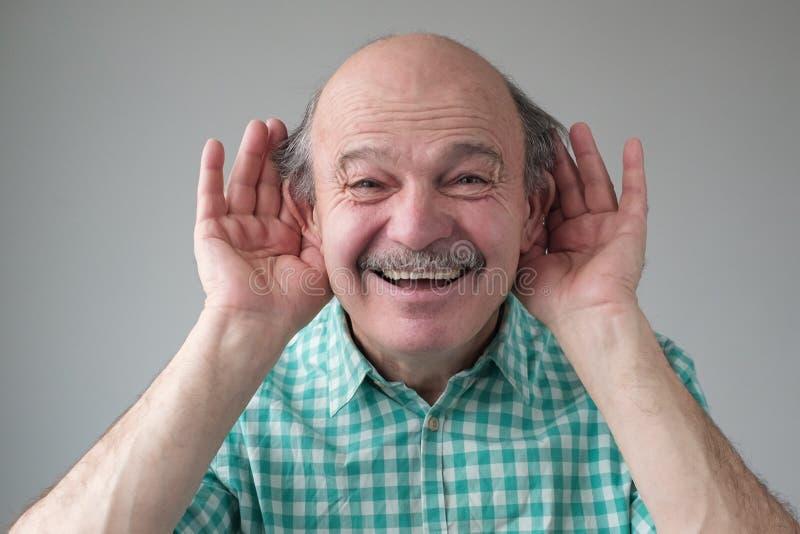 Man hört bei Gesprächen auf, hört Ohren, lächelt bei saftigen Klatsch stockfotos