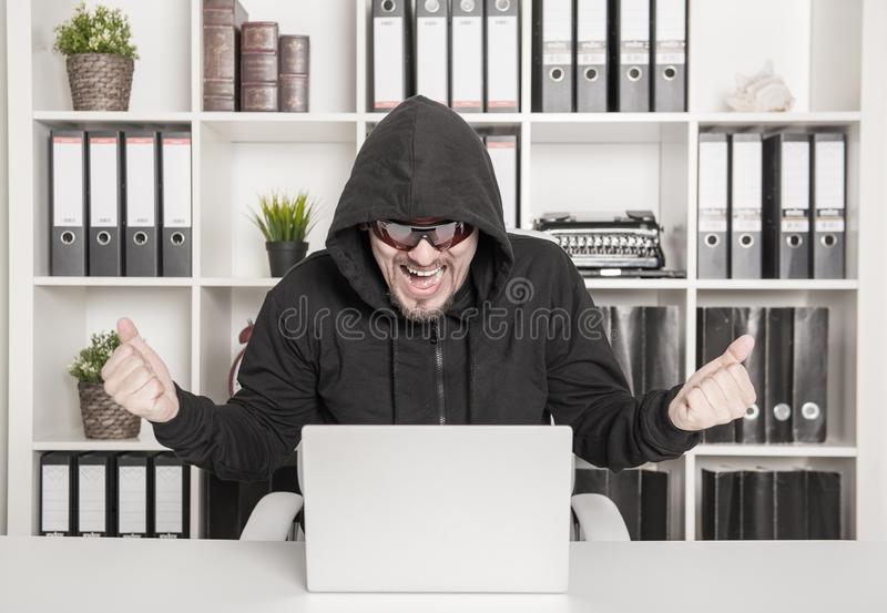 Man hacker using laptop and breaking open password in office royalty free stock images